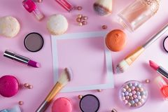 Make up products and macaroons. Frame with copy space on pink background stock photo