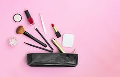 Make up products spilling out of a black varnished cosmetics bag on a pastel pink background stock photography