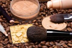 Make-up products to create fresh summer look. Concealer stick, highlighter, foundation, loose and shimmer golden powder with makeup brushes on coffee beans Stock Photos