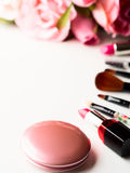 Make up products and tools with pink roses flowers on white Royalty Free Stock Images