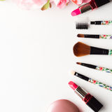 Make up products and tools with pink roses flowers on white Stock Photography