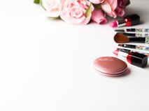 Make up products and tools with pink roses flowers on white Stock Image