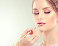 Make-up in progress. Beautification. Hand of make-up master, painting lips of young beautiful model. Make-up in progress royalty free stock photo