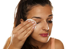 Make up removing. Young beautiful woman removing her make-up with cotton pad stock photo