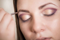 Make up salon. Make up artist doing professional make up of young woman royalty free stock photo
