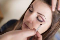 Make up salon. Make up artist doing professional make up of young woman stock photo