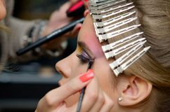 Make-up session. Beautiful young model getting fashion make-up stock photography