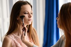 Make-up session for a beautiful girl. The stylist applies makeup to the girl royalty free stock images