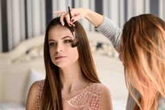 Make-up session for a beautiful girl. The stylist applies makeup to the girl stock images