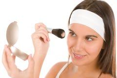 Make-up skin care - woman apply powder. Skin care - young woman apply powder with make-up brush watching mirror Stock Photos
