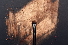 Make-up smeared on black Surface and beauty Brush. Creative Background with golden Make-up Cosmetics smeared on black Surface and beauty Brush Stock Images