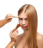 Make-up for tender beauty. Young beautiful woman with long blond hair applying make-up isolated on white background Stock Photography