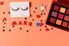 Make up text on an orange background. Professional trendy makeup products with cosmetic beauty products,  eye shadows, eye lashes. Brushes and tools. Top view royalty free stock photography