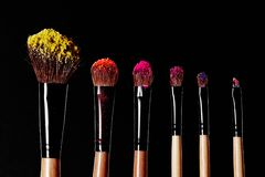 Make-up tools. Brush for makeup. Cosmetic brushes on black with bright dust splash. Pink, yellow, red shadows pigment stock photos