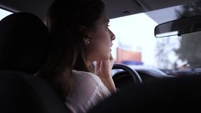 Make-up in transport. Breaking the law by a nice young woman. The brunette sits in the driver`s seat and applies shadows