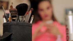Make up of unknown woman with make up brushes in foreground