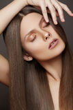 Make-up, wellness. Beautiful woman model with long straight hair, pure skin. Wellness. Ð¡osmetics. Portrait of woman with shiny long brown hair on gray royalty free stock image