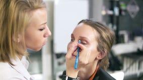 Make-up work. Make-up artist and model. Girl makeup with short fair hair. Makeup artist paints eyeliner lower eyelids stock video