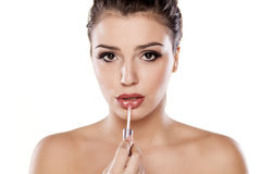 Make up. Young woman applying lip gloss Stock Photo