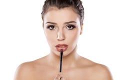 Make up. Young woman applying lip gloss royalty free stock image