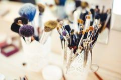 Make-upbürste im Glasbecher auf Frisierkommode stockbild