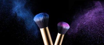 Make-upbürste mit rosa und blauer Pulverexplosion Stockfotografie