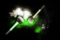 Make-upbürste mit weißem Pulver verschüttete Funkelnstaub auf schwarzem Hintergrund Make-upbürste auf neues Jahr ` s Partei mit h Stockbild