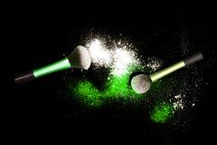 Make-upbürste mit weißem Pulver verschüttete Funkelnstaub auf schwarzem Hintergrund Make-upbürste auf neues Jahr ` s Partei mit h Lizenzfreies Stockfoto