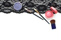 Make-upbürsten und -kosmetik auf schwarzer Spitze lizenzfreie stockfotografie