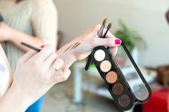 Make-upbürsten und -schatten in den Händen von Lizenzfreie Stockfotos