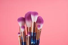 Make-upbürstensatz auf rotem rosa Pastellhintergrund Stockfotografie