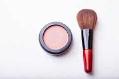 Make-upborstel en kosmetisch poeder op witte achtergrond Stock Afbeelding