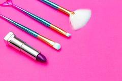 Make-upborstel en violet lippenstiftviooltje op roze achtergrond De ruimte van het exemplaar stock foto's