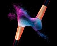 Make-upborstel met blauwe poederexplosie op zwarte stock afbeeldingen