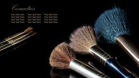 Make-upborstel op professioneel schoonheidsmiddel op zwarte backgrou stock afbeeldingen