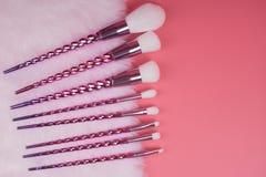 Make-upborstel op rode roze pastelkleurachtergrond die wordt geplaatst Royalty-vrije Stock Afbeelding