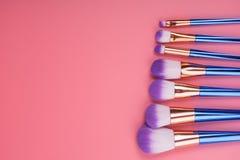 Make-upborstel op rode roze pastelkleurachtergrond die wordt geplaatst Stock Afbeelding