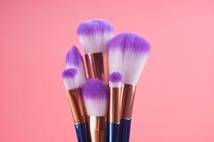 Make-upborstel op rode roze pastelkleurachtergrond die wordt geplaatst Royalty-vrije Stock Fotografie