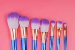 Make-upborstel op rode roze pastelkleurachtergrond die wordt geplaatst Stock Afbeeldingen