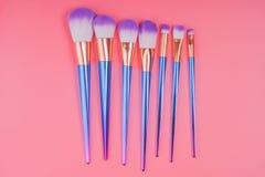 Make-upborstel op rode roze pastelkleurachtergrond die wordt geplaatst Stock Fotografie