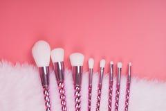 Make-upborstel op rode roze pastelkleurachtergrond die wordt geplaatst Stock Foto