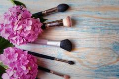 Make-upborstels en hydrangea hortensia op abstracte houten blauwe backgro Stock Afbeelding