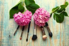 Make-upborstels en hydrangea hortensia op abstracte houten blauwe backgro Stock Afbeeldingen