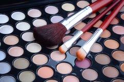Make-upborstels en oogschaduwwen Stock Foto