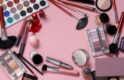 Make-upborstels en schoonheidsmiddelen op een roze achtergrond stock afbeelding