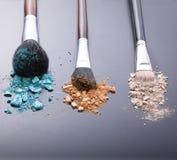 Make-upborstels op achtergrond met kleurrijk poeder Stock Foto's