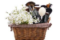 Make-upborstels in voederbak met bloemen worden geplaatst die muur Geïsoleerde Wh stock afbeeldingen