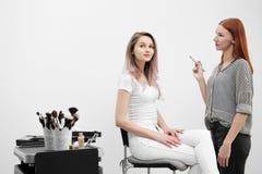 Make-upkünstler-Rothaarigemädchen macht Make-up schönes Blondinemodell auf weißem Hintergrund Nahe bei dem Wagen mit Werkzeugen stockbilder
