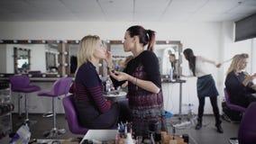 Make-upkünstler arbeitet, Modell für zukünftiges Schießen vorbereitend Weiblicher Meister des Brunette trägt Kosmetik auf Kunde ` stock video footage