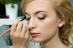 Make-upkünstler, der Farblidschatten auf dem Auge des Modells, nahes u anwendet Stockfotografie